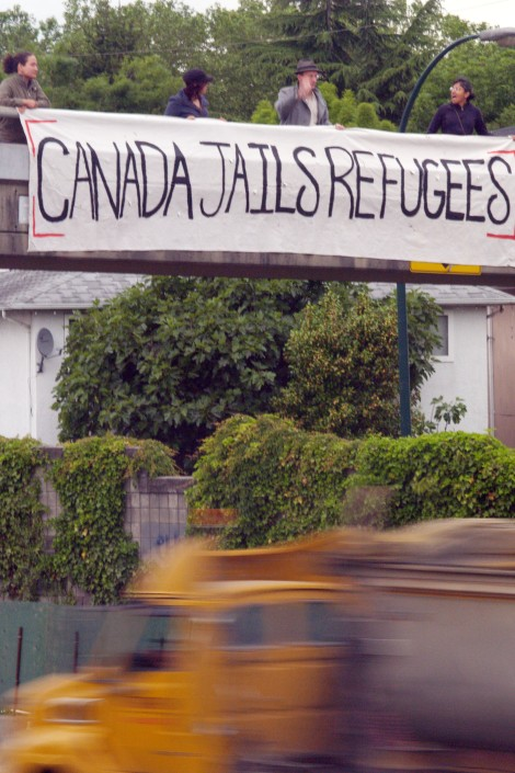 """No One Is Illegal Vancouver dropped a """"Canada Jails Refugees"""" banner during morning rush hour in opposition to the government's anti-refugee Bill C-4. Photo by David P Ball"""