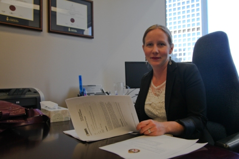 Laura Best, an immigration and refugee lawyer with Embarkation Law Group, examines documents she helped draft that successfully encouraged Toronto police to adopt a 'don't ask' policy toward undocumented migrants. In cases without warrants, she'd like Transit Police to do the same. Photo by David P. Ball