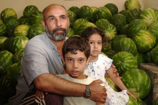 A watermelon farmer in southern Lebanon holds his children. Photo David P. Ball 2006